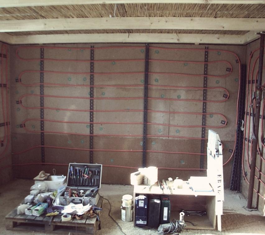 Einbau Wandheizung auf Holzweichfaserdämmplatten und mit Lehm verputzt.